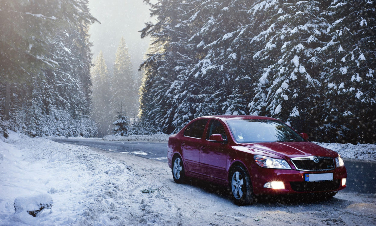 red car driving in snow