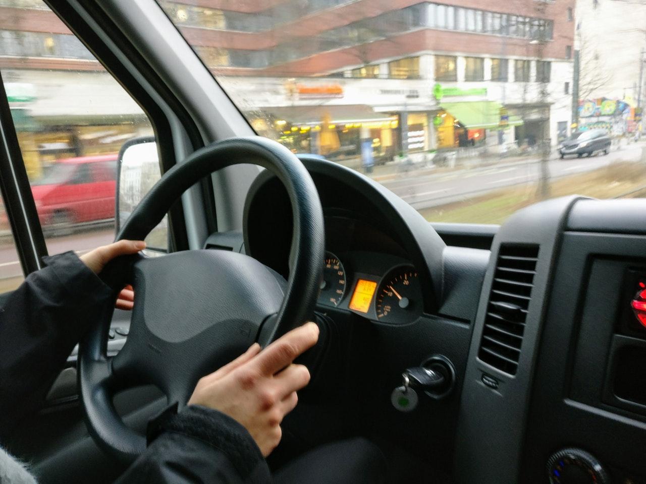 Man holding steering wheel in car
