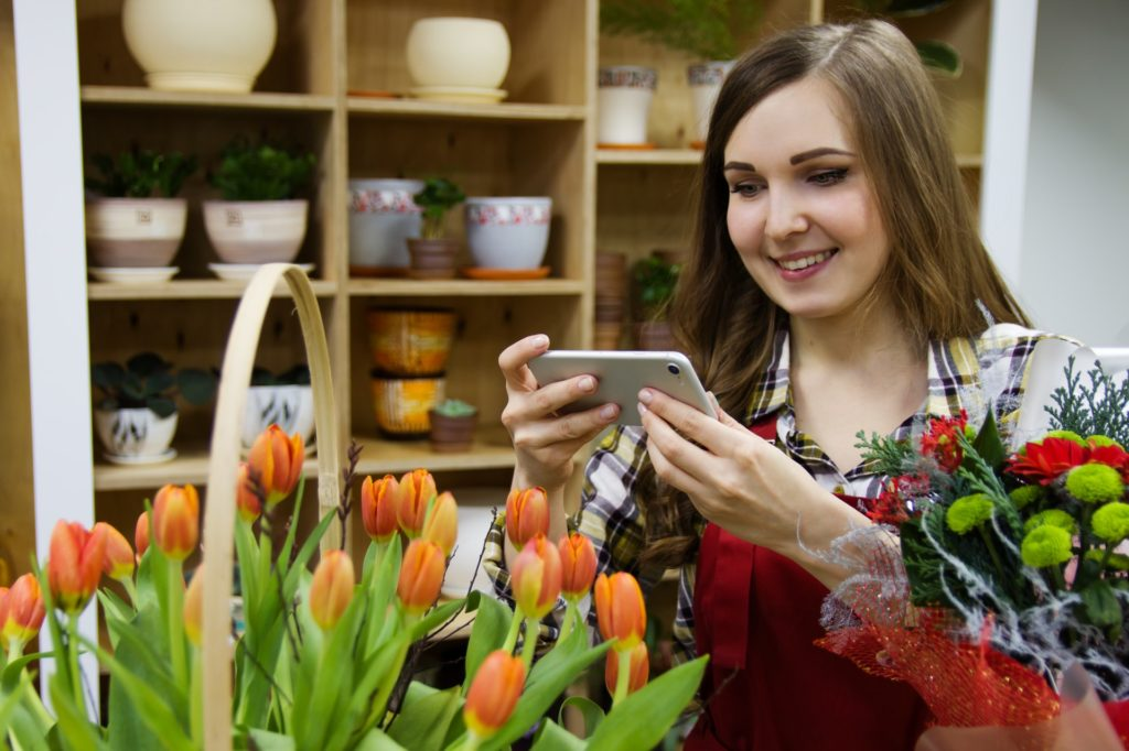 Woman taking photo of tulips in shop