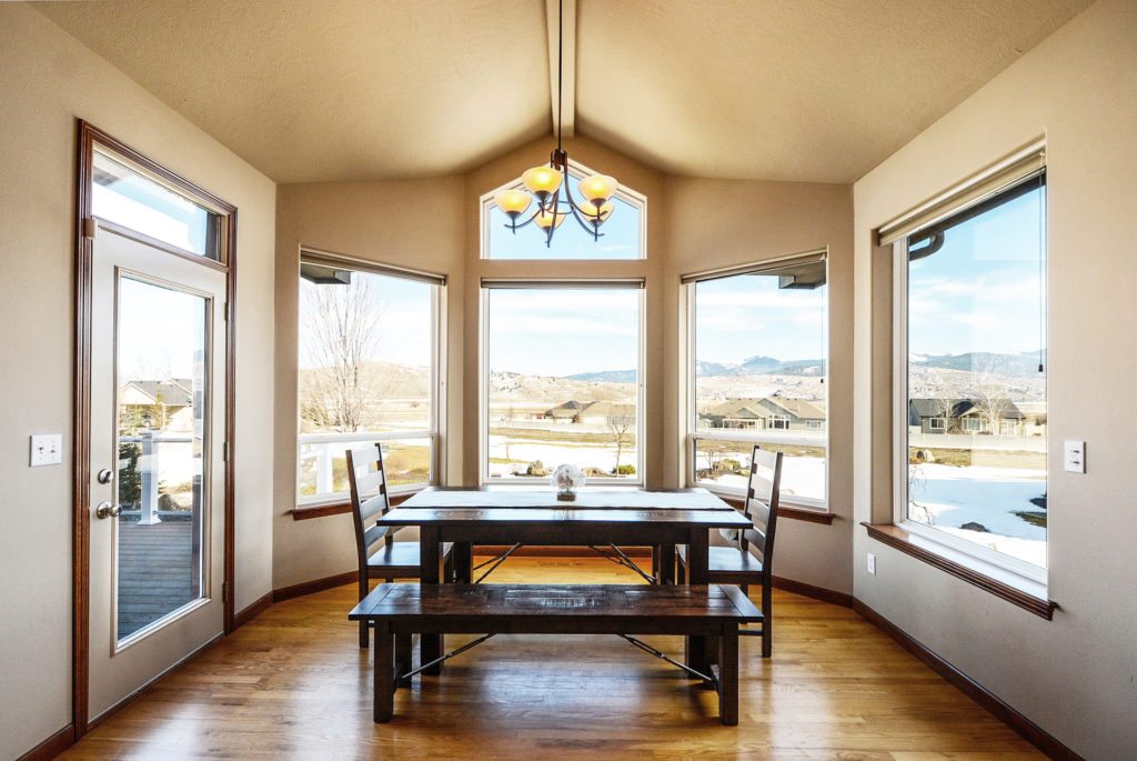 Large windows in a home's dining room look out on a snowy yard