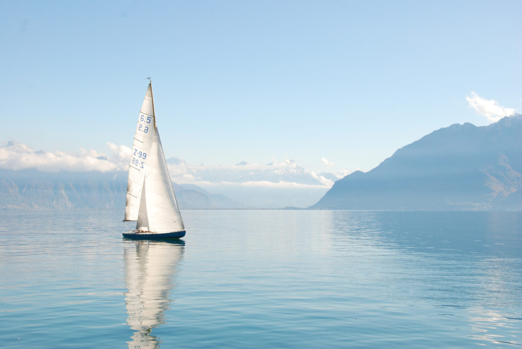 A sailboat on a sunny day with a view of the mountains.