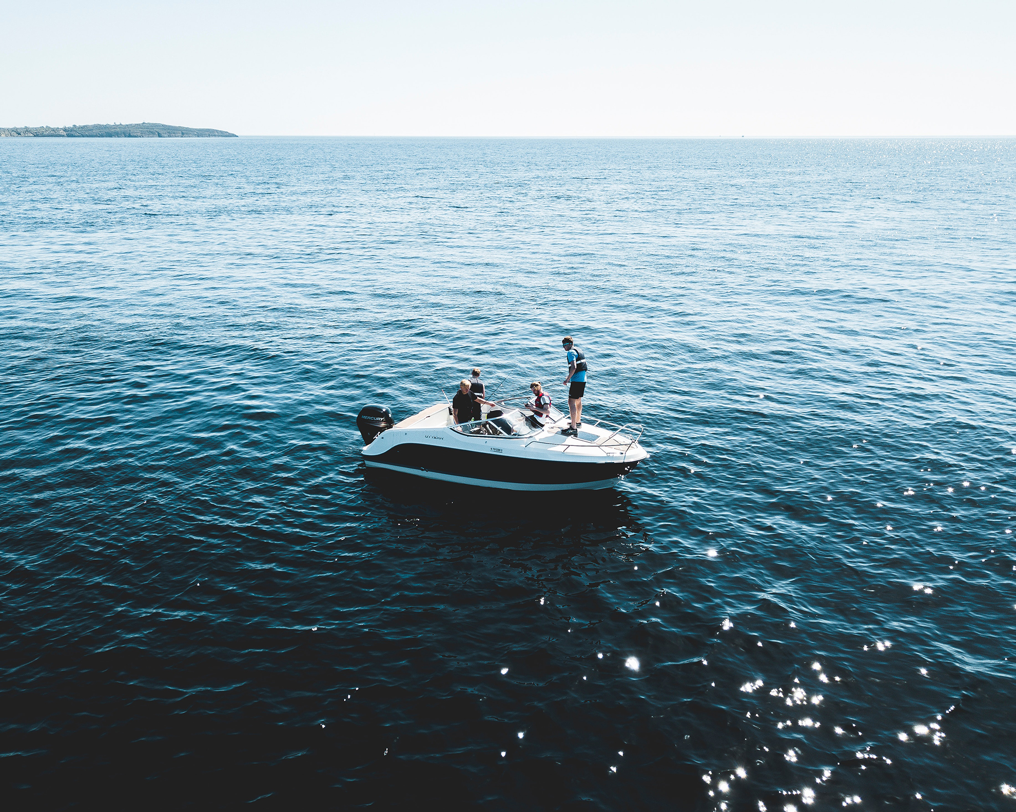 Three people on a white speedboat in a summer day.