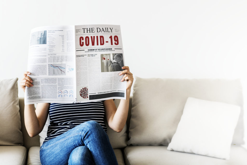 Person holding newspaper with covid-19 information