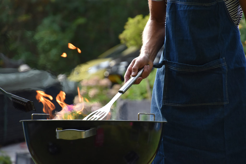 Man holding barbecue kitchen tool to move burguers at a grill