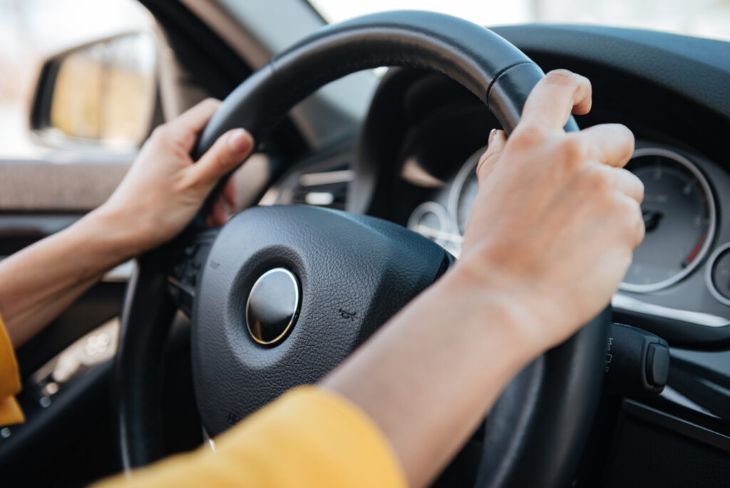 Close-up of female hands on steering wheel while driving a car