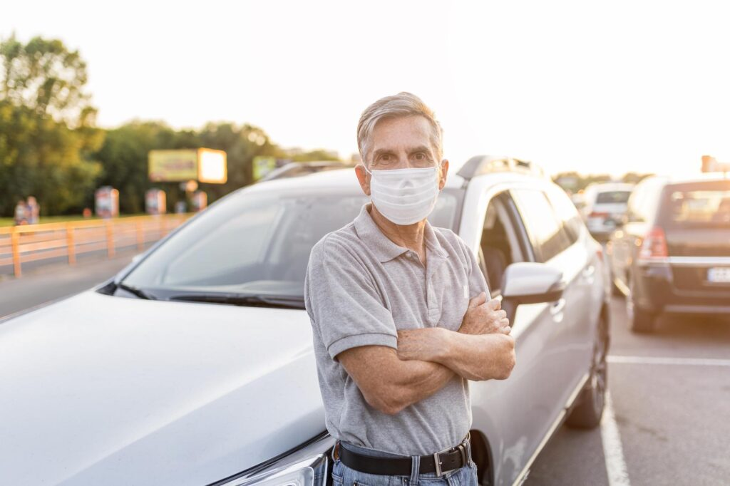 Older man wearing a facemask posing in front of his car
