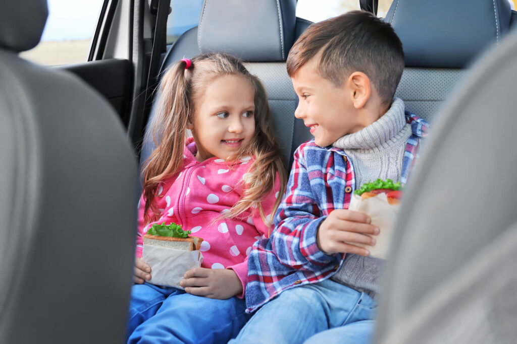 Alt text: Two kids smiling eating sandwiches in a car.