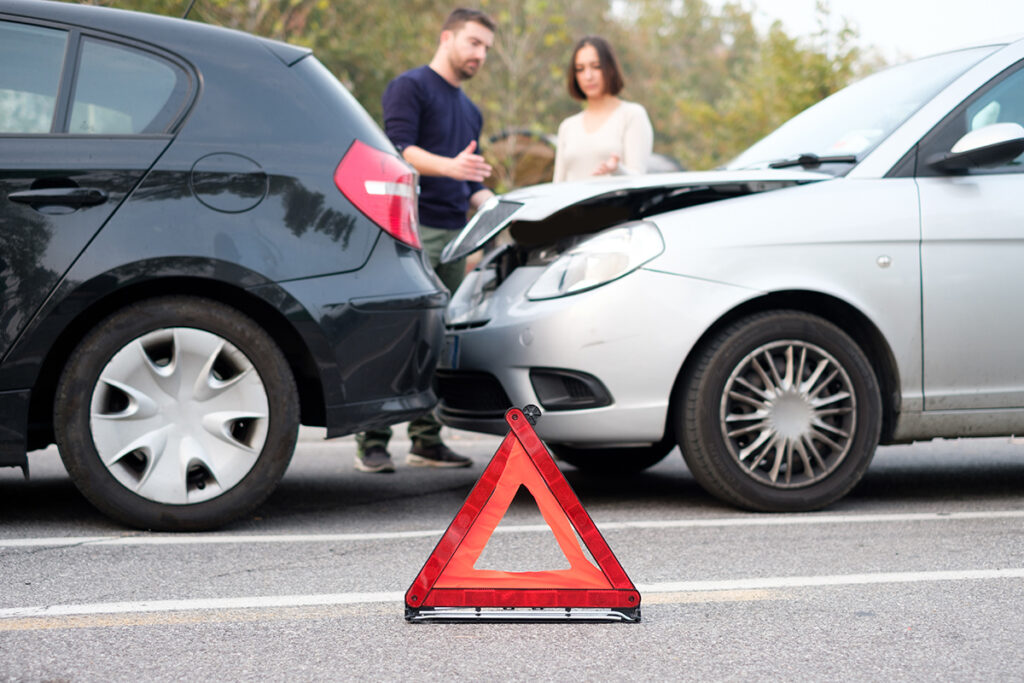 People and cars in the aftermath of an auto accident exchanging insurance information.
