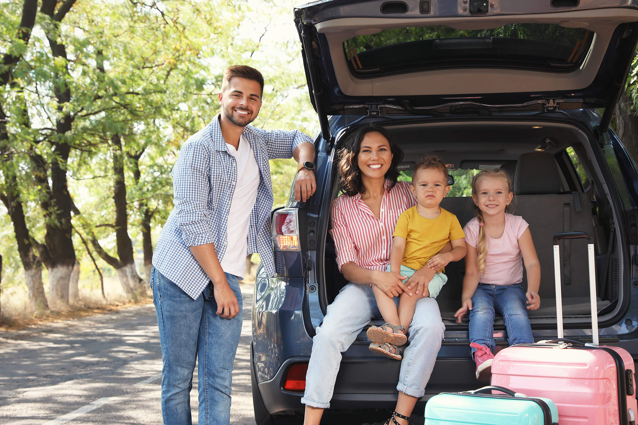 Alt text: Happy family on a road trip with suitcases.