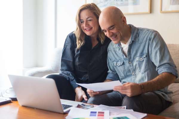 Happy couple of clients talking to interior designer through video call. Caucasian man and woman in casual studying wall paint swatches and using laptop. Renovation concept